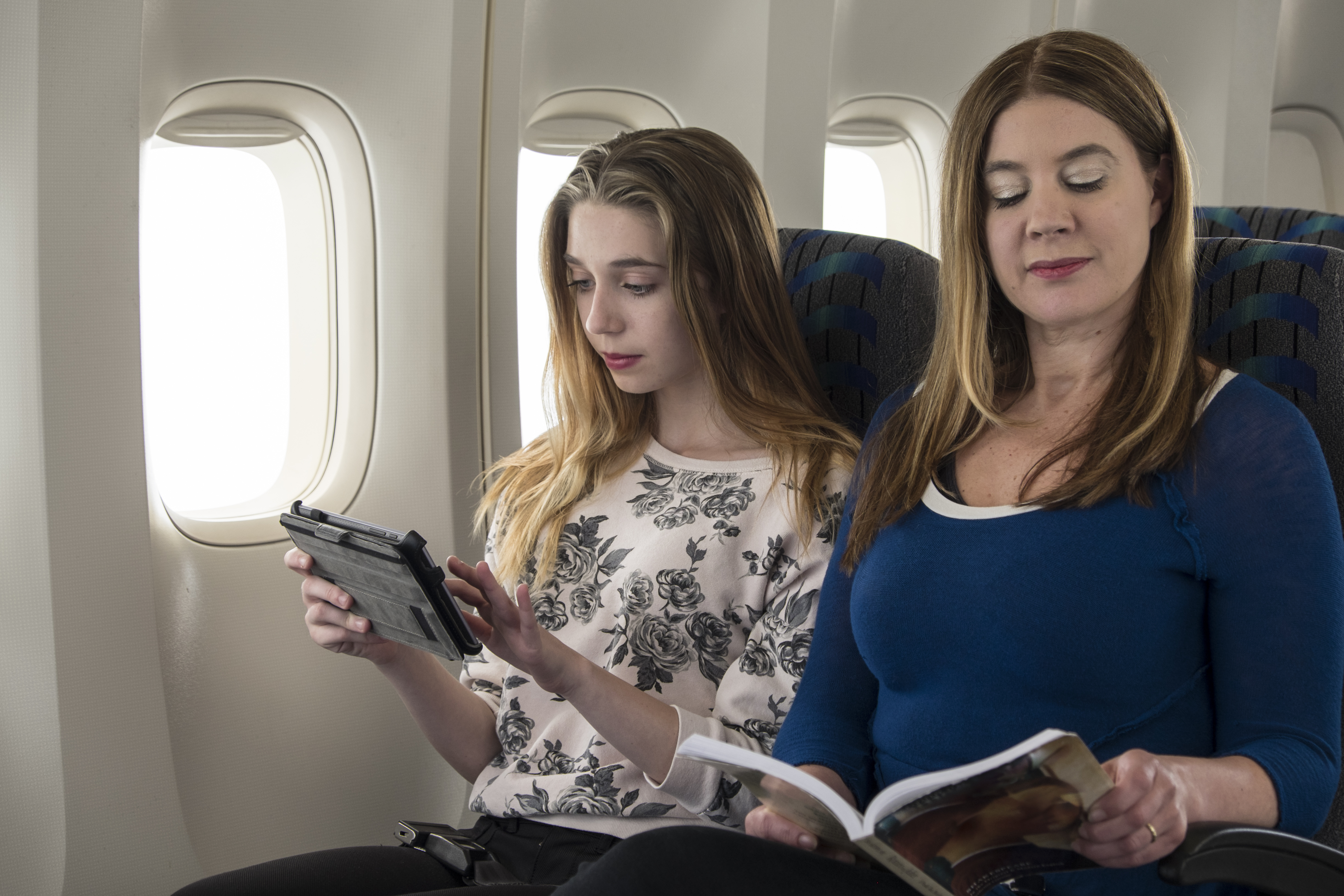 Two women seated in an airplane using a tablet and reading a book